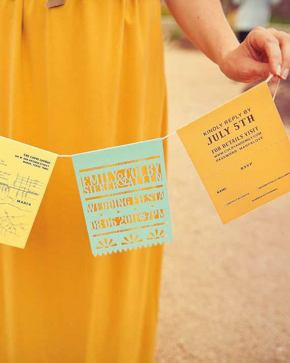 """Festive invitations were strung together like Mexican """"papel picado"""" flags at this Marfa wedding. Southern Fried Paper used paper in the couple's wide range of hues."""