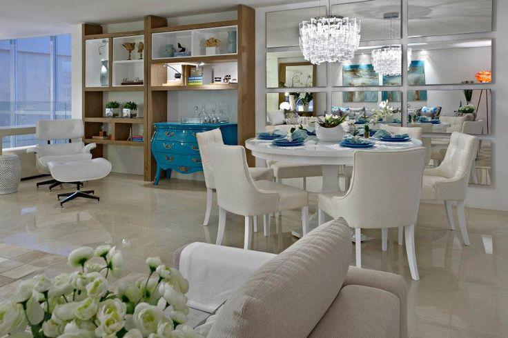 Mesa de jantar em laca branca extra brilho + cadeiras de fibra. Gosto da composição de quadros sobre o aparador. Projeta Beto Galvez e Nórea De Vitto, via Arkpad.