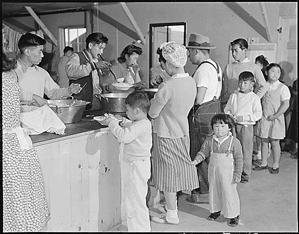 http://www.bookmice.net/darkchilde/japan/japan/heart/21-2189a.jpg Dinner is served caffeteria style to young and old in the mess halls at the Heart Mountain Relocation Center.
