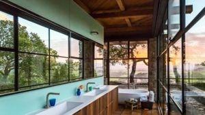 Wand zu Wand Fenster erstellen die optische Illusion des Raumes in diesem Badezimmer.
