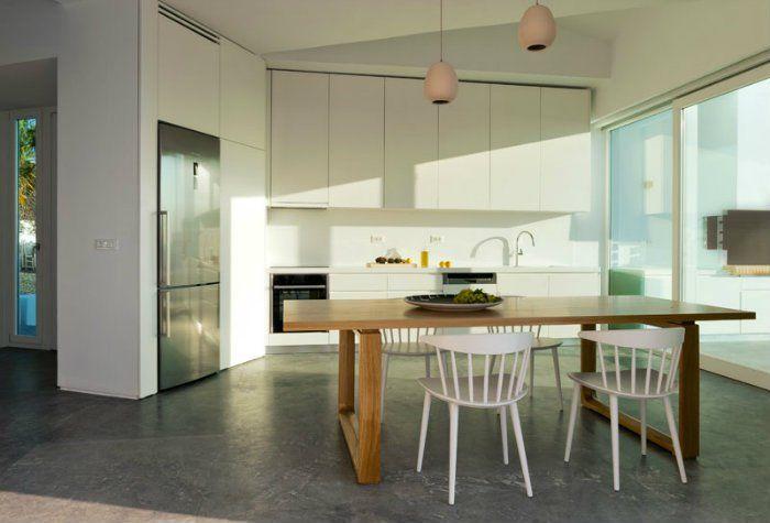 Η κουζίνα έχει λευκά ντουλάπια που μπλέκονται με τους τοίχους και μαρμάρινο ματ γκρι πάτωμα.
