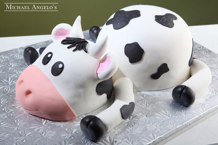 Baby Cow #25Animals  This design is cake hand crafted in the shape of a cow. The entire cake is iced in fondant with black cut-outs to make it look like the real thing. The face is designed to appear like a baby cow. Perfect for any baby shower or any celebration with a cow or theme!