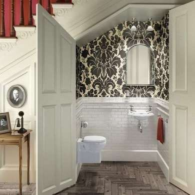 Under Stair powder room with small toilet and sink, wainscoting and loud black and white wallpaper