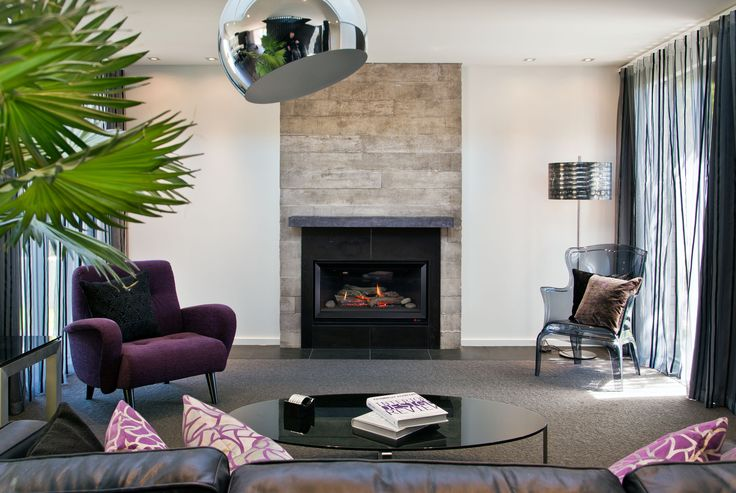 The living room with a concrete block fireplace serving as a focal point.