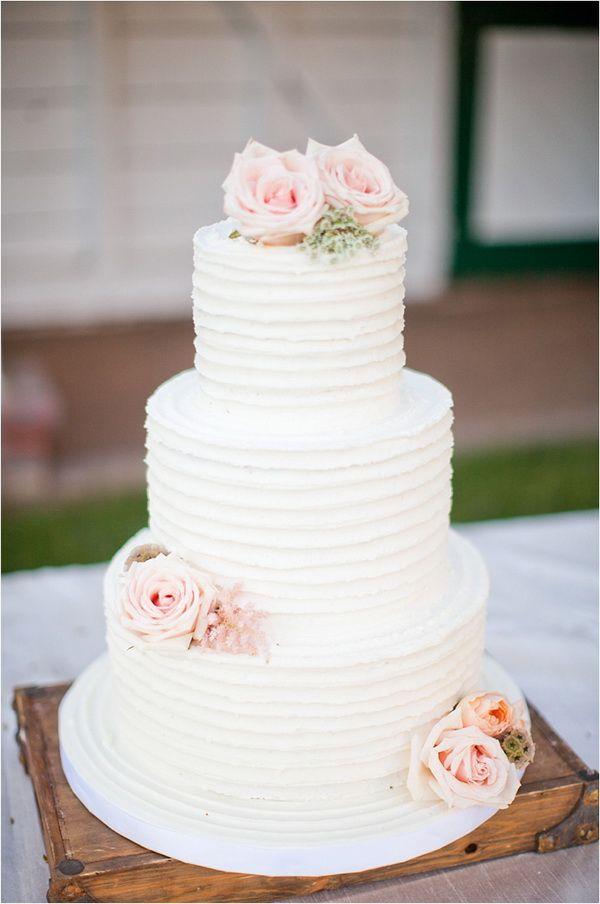 three tiered white wedding cake with pink rose