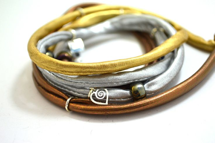 Gold, silver and copper lycra cord embellished with glass and metal beads, metal charms and handmade red evil eye charm. Length approx. 100 cm. Five (5) turns round the wrist. Adjustable bracelet, fits to all wrist sizes. Comes in a gift box. Tip: Try it as a necklace !!!! http://www.freeartstyle.com/jewellery/bracelets/141/gold,-silver-and-copper-lycra-cord-%E2%80%93-hearts-detail