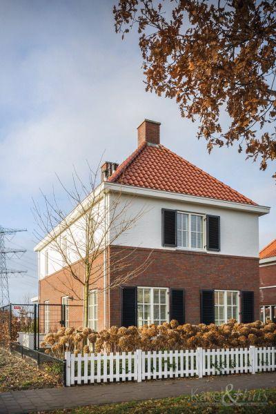 Klassieke woning, jaren-dertig woning. Rode pannen, rode bakstenen,  een wit element op de voorgevel en witte hekjes bij de voortuin.