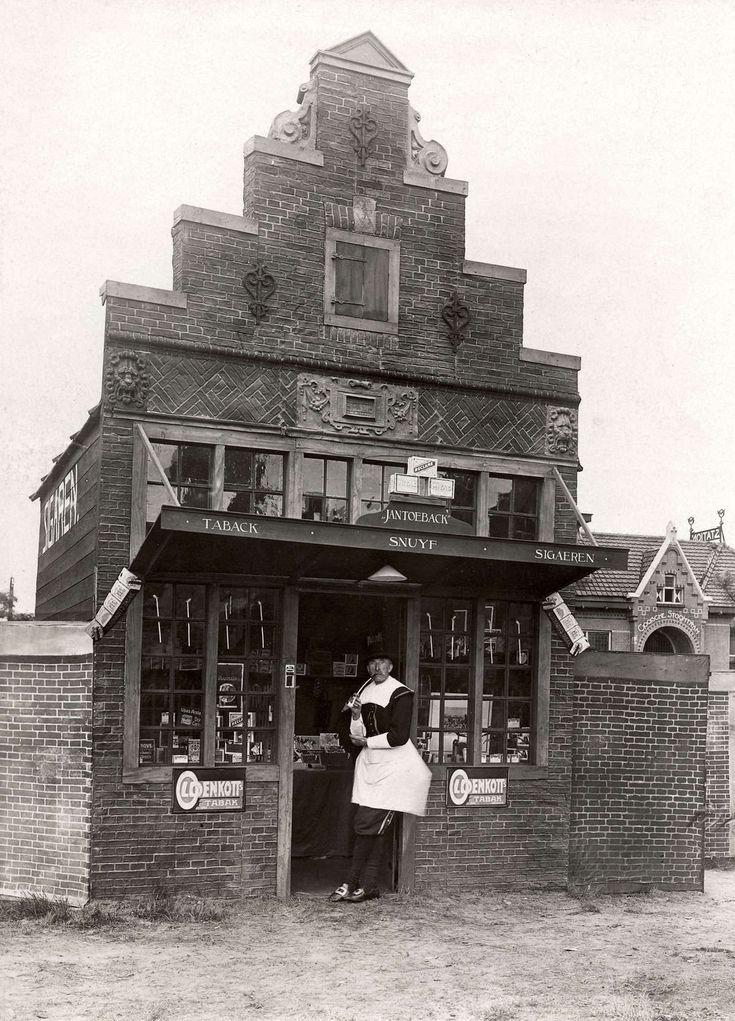 Steden en dorpen. Feestelijkheden in Laren(N-H). In het dorp is een decor van historische huizen opgebouwd. Voorbeeld van een sigaren- en tabaks winkeltje met daarvoor de verkoper. Laren, 1914 #Laren #Gooi #NoordHolland