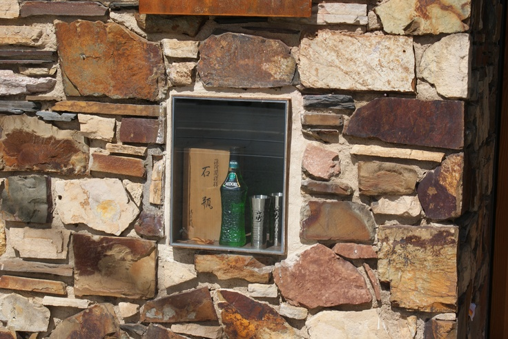 Considered wall paving looks fabulous with a hidden cabinet full of old bottles - like like like! xx