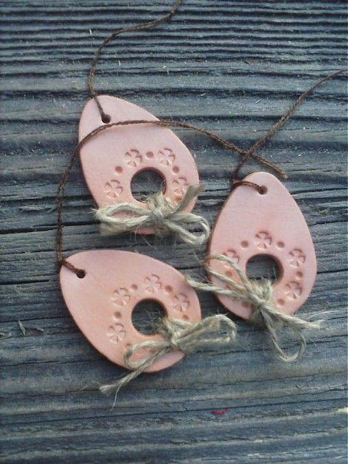 Ručne vyrobená ozdôbka z hnedej (terakotovej) keramickej hmoty v tvare vajíčka. Ozdobená je ručne vytlačeným kvetinovým vzorom a mašličkou z jutového špagátika. Každé vajíčko je z oboch str...