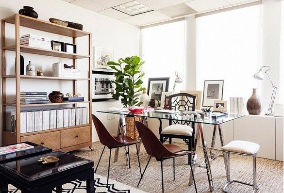 Bright, feminine office with glass desk, vintage chairs, and styled bookshelves.