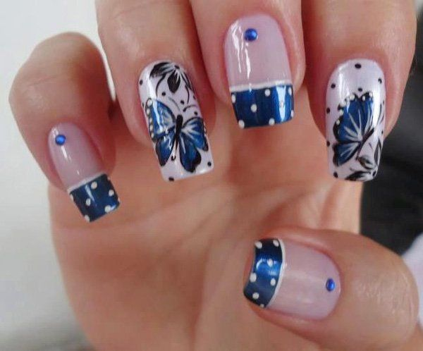 Metallic blue themed butterfly nail art design. The nails are French tipped with metallic blue polish and white polka dots. The other nails are painted in matte white for base color and black polka dots. Majestic blue butterflies in glorious detail are then painted on top and accentuated with blue beads.