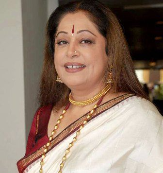 Kiron Kher resplendent in red and white with traditional jewellery. Description by Pinner Mahua Roy Chowdhury.