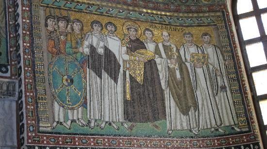 Dettaglio del mosaico di Giustiniano e il suo seguito della basilica di San Vitale (vedi Pin correlato). Il manto dell'imperatore è in porfido, su uno sfondo dorato privo di profondità; la fibula a tre pendagli rimanda alla trinità; le pantofole sono ricche di gemme preziose; le espressioni sono anonime, se non per qualche accenno di ruga.
