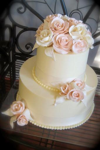 Torta de boda decorada con rosas de color rosa pastel hechas de azúcar.