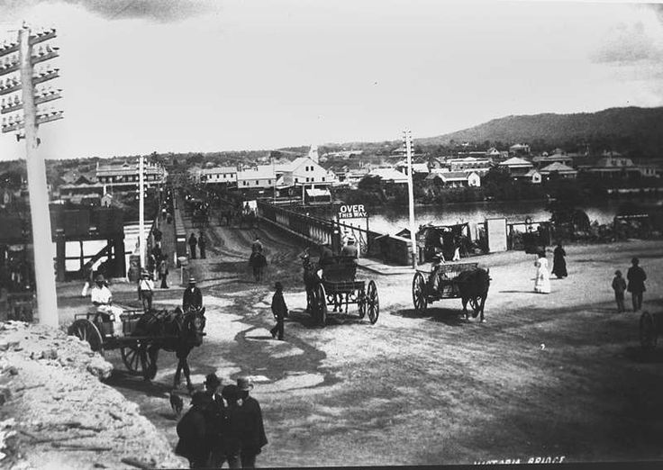 Horsedrawn carriages and pedestrians at the northern approach to the first permanent Victoria Bridge, Brisbane, ca. 1885