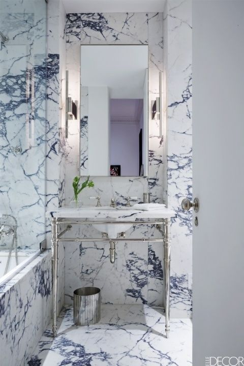 The walls and floors in a New York City apartment are sheathed in Calacatta Viola marble with silver furnishings.