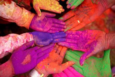 Indian Almanac Highlighting Hindu Festivals for 2015. Top angle view of human hands smeared with holi - Visage/Stockbyte/Getty Images