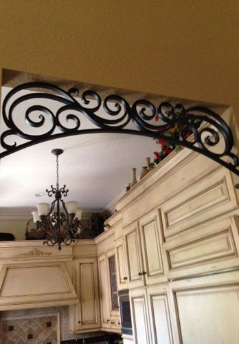 This homeowner in Orange, CA wanted Angels Ornamental Iron to create a custom wrought iron arch in the entrance to this kitchen. This wrought iron scroll ...