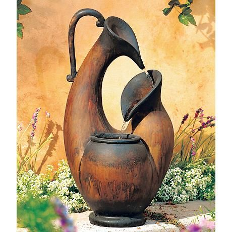 This tabletop fountain references the classic Mediterranean jug shape with its elongated shapes, curled handle, and spouted water falls.