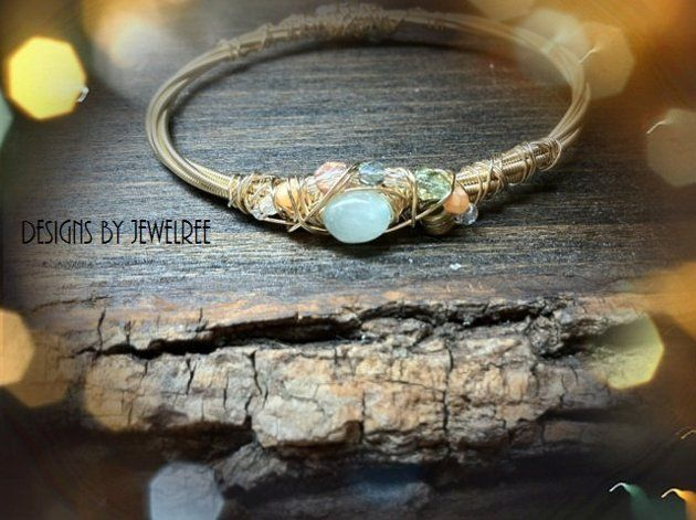 You would never tell these beautiful bracelets are made from guitar strings. Designs By Jewelree creates these beachy bangles adorned with pastel beads. Designs By Jewelree specializes in recycled and mixed metal jewelry.