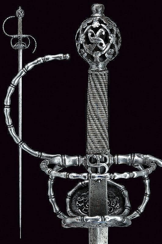 "A pierced rapier. Dating: circa 1600. Italy. Strong, straight blade of lozenge section, tang with crowned stamp ""S""; iron hilt richly chiselled and pierced, double valve, border, guard, parry rings and rings all featuring baluster-shaped decorations, the valves, quillon-block and pommel pierced with floral motifs; grip with silver wire binding and moor's heads. Llength 130 cm."
