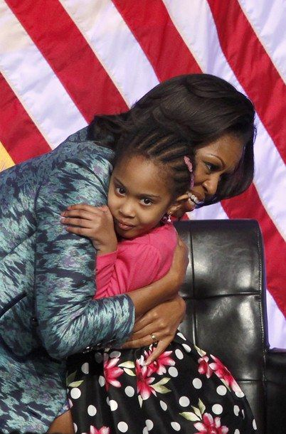 First Lady Michelle Obama hugs Piper Shillingford, 4, from a Brooklyn Montessori School after she presented a donation at the ground breaking ceremony