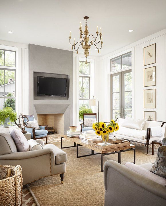 Modern French chic living room with gray stone fireplace, flat screen over fireplace, curvy French gray sofas, French settee, gray window moldings, gray doors and blue French chairs.