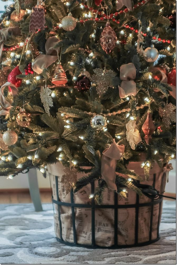 Sit the tree on a concrete block to raise it above the edge of a basket. This one lined in burlap.