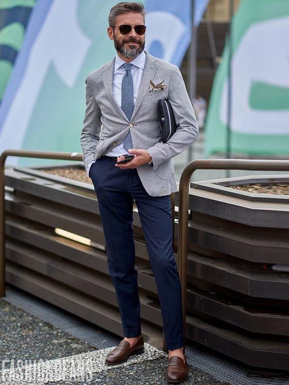 Acheter la tenue sur Lookastic: https://lookastic.fr/mode-homme/tenues/blazer-chemise-de-ville-pantalon-chino/21398 — Chemise de ville blanche — Cravate géométrique bleu marine — Pochette de costume imprimé beige — Blazer en laine gris — Pantalon chino bleu marine — Slippers en cuir bruns foncés — Lunettes de soleil brun foncé