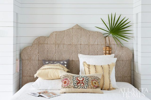 A custom headboard and colorful throw pillows from Interior Philosophy add punch to the first-floor bedroom.