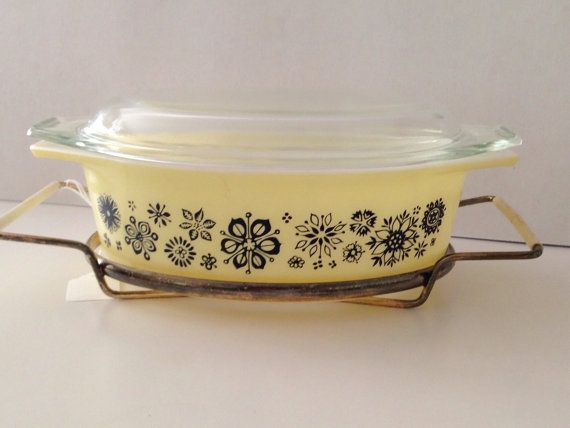 Gorgeous Pyrex Pressed Flowers 043 casserole with lid and cradle. This base is in excellent condition with very little wear. Pattern is excellent. I dont think it was used very much. The cradle us a bit tarnished but easy to clean and the lid is chipped.