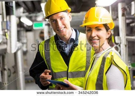 Engineers working in temperature control room of large building - stock photo
