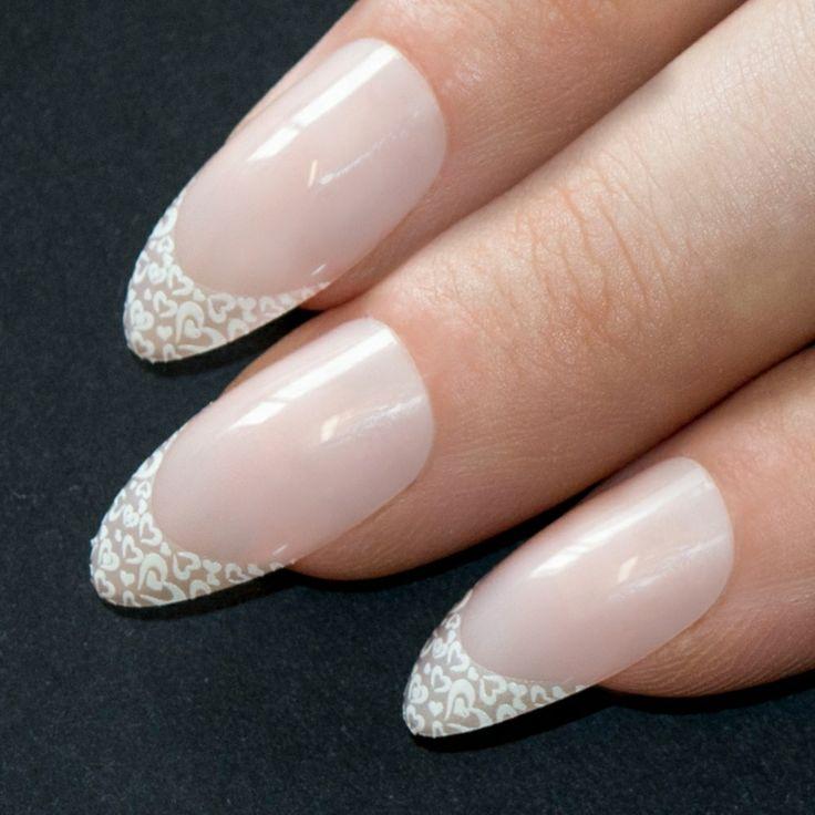 Decorare la french manicure con applicazioni pizzo a forma di cuoricini di colore bianco
