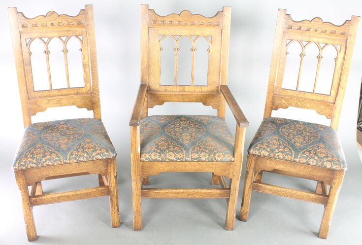 LOT 912, A set of 12 oak Gothic style high back dining chairs with arcaded backs and upholstered seats, raised on turned and block supports, comprising 8 carvers and 4 standard SOLD £600