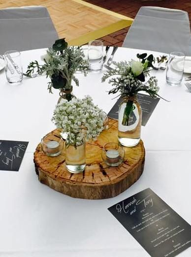 Rustic centrepiece with a collection of 3 vases with fresh flowers and candles on a real wood base. www.houseofthebride.com.au