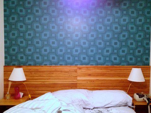 A arquiteta Livia Cavalca combinou a cabeceira com aparência de madeira aos papeis de parede desenhados por Marcelo Rosembaum para a Bobinex. Uma fita de LED destaca as estampas durante a noite.