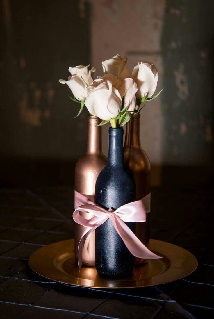 Designed by Bethany's Bouquets. Wine bottle centerpiece for wedding. #roses #blush #blushpink #gray #blushpinkandgray #winebottles #wine #chargers #elegant #simplicity #wedding #threeinone #bow