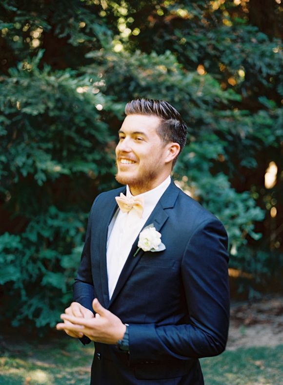 Classic navy blue tuxedo with bow tie and flower lapel for grooms.