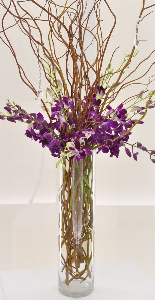 Beauty in Simplicity: Tall cylinder vase with curly willow submerged and coming out of the vase with purple dendrobium orchids and hanging crystals.