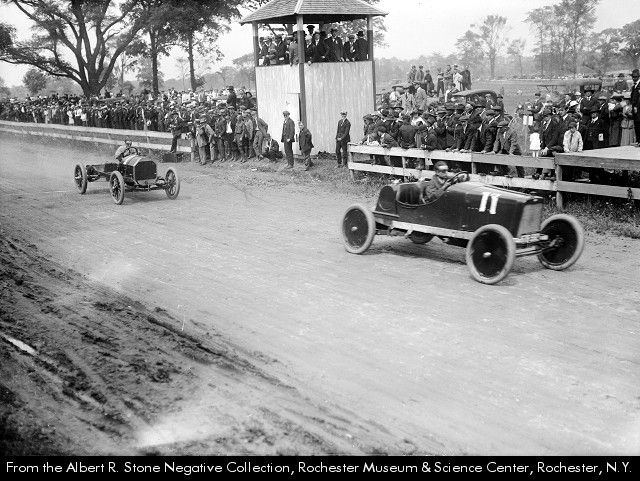 c.1918 Racing cars on a dirt track probably at the Livingston County Fair Grounds in Avon. A wooden fence separates the track from a crowd of people, mostly men. At least 12 stand in a raised, roofed, spectator platform. Trees, a field, and parking area fill the background. Automobile racing in New York near Rochester.
