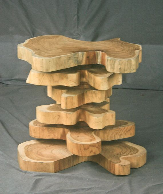 """This handmade, live edge end table is an incredibly unique piece, sure to draw the attention and admiration of anyone who enters your home or office. The 2"""" thick teak slabs were responsibly harvested from a farm in Costa Rica, and stacked to create a surface 20"""" high. Each slab has an unusual shape, smooth surfaces, and a beautiful grain pattern. The center supports could be made with steel but are pictured as made from wood. These tables also function perfectly as unique nightstands and…"""