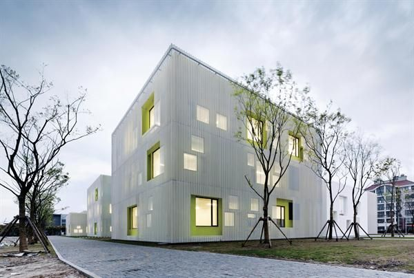 The perforated-metal-screen-clad volumes of the Youth Center are interspersed with white-washed volumes, which the architects used, in combination with the gray brick pavers, to nod back to the traditional building typologies of the region. The windows not only admit daylight, but also help express the interior spaces and program on the minimalist - Youth Center of Qingpu - Atelier Deshaus