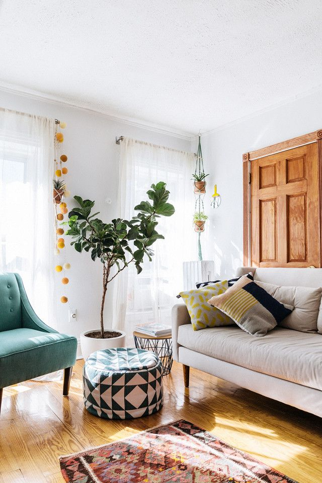 Cozy Scandinavian inspired living space with a simple IKEA sofa, a Turkish rug, and a green armchair