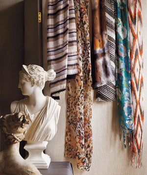 Patterned light scarves hanging on wall next to white sculpture