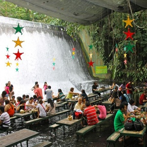 Villa Escudero Plantations and Resort, in San Pablo City, Philippines  - The resort offers bamboo rafting, tropical hikes, bird watching, coconut harvesting, and, as shown here, a dining space beside a natural waterfall. Enjoy your meal as the cool spring water runs over your feet. This is the life!