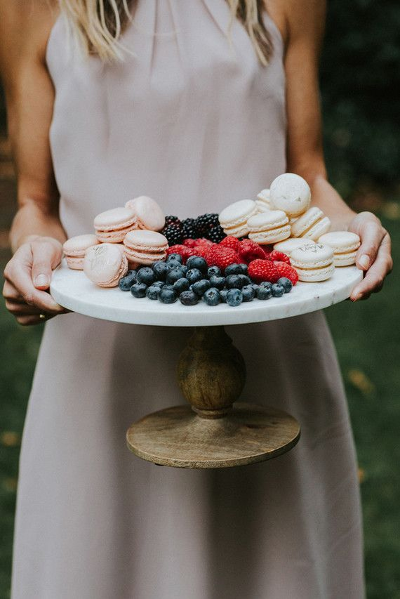 macaron and fruit dessert spread on a cake stand for added elegance