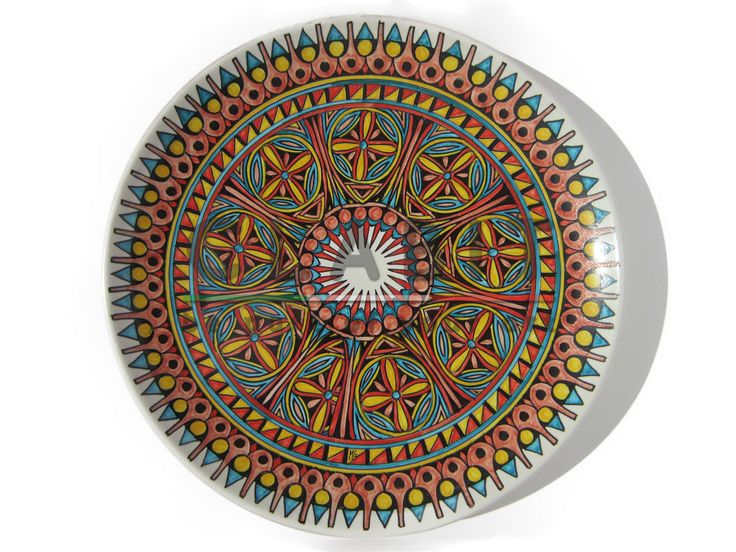"""The decorative plate """"ESPLENDOR GEOMÉTRICO"""" (SERIE ELLADE) shows a modern decoration with coloured geometric shapes. These forms draw inspiration from the Greek architecture designing an ideal fusion between lines and colours. A hook to hang the plate on the wall is included."""