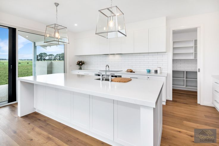 Beautiful country style kitchen with white cabinets, white stone bench tops, subway splashback tile and butlers pantry