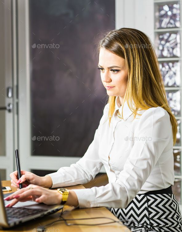 Female designer in office working with digital graphic tablet and laptop by Satura_. Female designer in office working with digital graphic tablet and laptop. Photography retoucher sitting at desk and l...